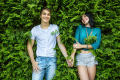 Young couple holding hands on the back is bright green foliage. Royalty Free Stock Photography