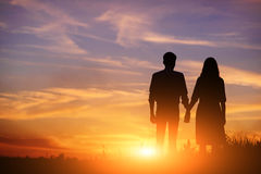 Young couple is holding hands on a background sunset silhouette.  Royalty Free Stock Photography