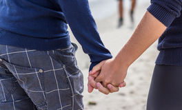 Young couple are holding hands. A young couple holding hands on the beach royalty free stock photography