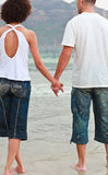 Young couple holding hands on the beach Royalty Free Stock Image