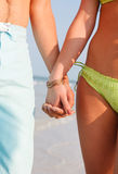 Young Couple Holding Hands on the Beach Stock Photo