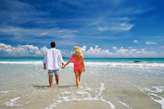 Young couple holding hands at beach enjoying romance. Royalty Free Stock Images