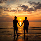 Young couple holding hands on the beach at sunset Royalty Free Stock Photography