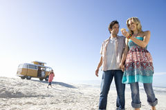 Young couple holding hands on beach, woman looking at shell, low angle view Stock Photo