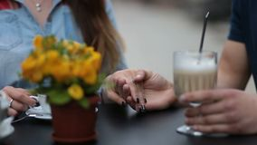 Young couple holding hands at the cafe, closeup stock footage