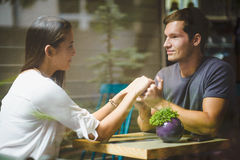 Young couple holding hands in cafe Stock Images