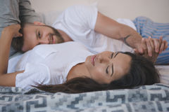 Young couple holding hands, embracing and relaxing on bed Royalty Free Stock Image
