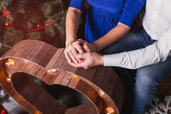 Young couple holding hands in front of a Christmas tree Royalty Free Stock Images
