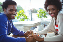 Young couple holding hands while having coffee Stock Photos