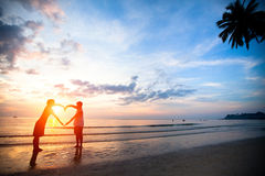 Young couple holding hands heart-shaped on the sea beach Stock Images