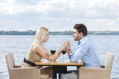 Young couple holding hands while looking at each other at outdoor restaurant by lake Royalty Free Stock Photography