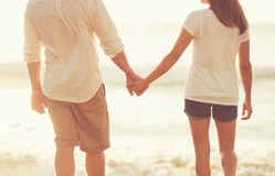 Free Young Couple Holding Hands On The Beach At Sunset Royalty Free Stock Photo - 60216965