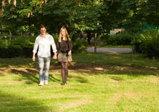 Young couple holding hands in the park. Stock Photos