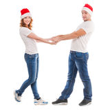 Young couple holding hands in red hats Royalty Free Stock Photography