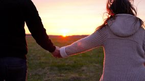 Young couple holding hands run through a wide field, having fun outdoors. Man and woman running away on the meadow stock video footage