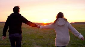 Young couple holding hands run through a wide field, having fun outdoors, slow motion stock video footage