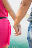 Young couple holding hands by the sea. Young couple holding hands. Close up outdoor Royalty Free Stock Photography