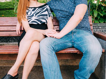Young couple holding hands while sitting on the bench.  Stock Image