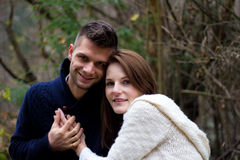 Young couple holding hands and smiling happily. In the forest Royalty Free Stock Photography