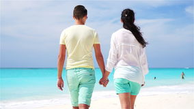 Young couple holding hands at tropical beach. Closeup SLOW MOTION. Happy couple together on the beach holding hands stock video footage