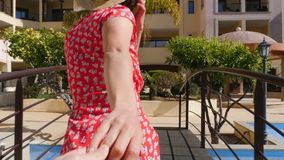 Young couple holding hands walking on the bridge. Young woman leading a man by the hand through the palm trees on the bridge stock footage