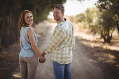 Young couple holding hands while walking on dirt road at olive farm Stock Images