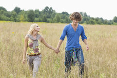 Young couple holding hands while walking through field Stock Image