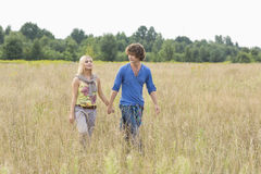 Young couple holding hands while walking through field Royalty Free Stock Image