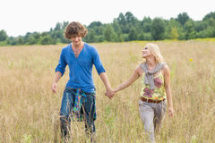 Young couple holding hands while walking through field Royalty Free Stock Photography