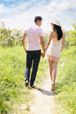 Young couple  holding hands. Young couple walking in the park holding hands Royalty Free Stock Image