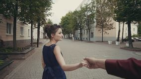 Young couple holding hands woman leading boyfriend running in street stock video footage