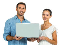 Young couple holding laptop and looking at camera. On white screen stock images
