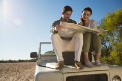 Young couple holding map on tire over off road vehicle Stock Photo