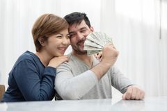 Young couple holding money for buy their new house. Happy Young couple holding money for buy their new house. US Dollar bills. Saving stock photo