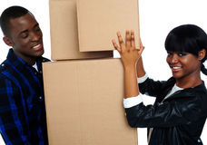 Young couple holding and moving boxes Stock Images