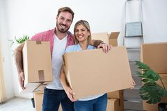 Young couple holding and packing boxes for moving. Young couple packing boxes for moving to a new home Stock Photography