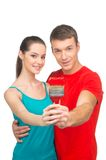 Young couple holding paintbrush together. Royalty Free Stock Photography