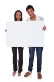 Young couple holding placard Stock Images