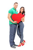 Young couple holding a red heart Royalty Free Stock Photo