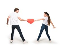 Couple with heart quarreling. Young couple holding red heart and quarreling, isolated on white Royalty Free Stock Image
