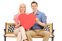 Young couple holding a red heart seated on a bench. Young couple holding a big red heart seated on a wooden bench and looking at the camera isolated on white stock photos