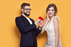Young couple holding red heart. Standing on a yellow background Royalty Free Stock Images