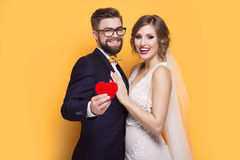 Young couple holding red heart. Standing on a yellow background Royalty Free Stock Image