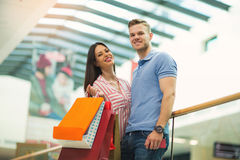 Young couple holding shopping bags in mall. Happy beautiful young couple holding shopping bags and smiling while doing shopping in mall Royalty Free Stock Photos