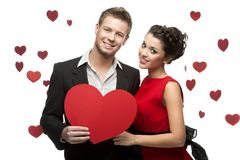 Young couple holding sign in form of red heart Stock Photos