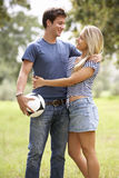 Young Couple Holding Soccer Ball In Countryside Stock Image