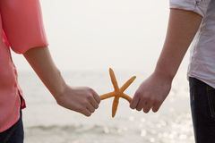 Young Couple Holding Starfish Stock Image