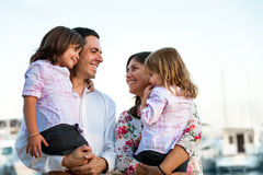Young couple holding their kids in arms outdoors. Close up family portrait of young couple holding their kids in arms outdoors Stock Image