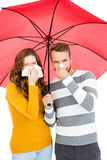 Young couple holding umbrella and wiping nose Royalty Free Stock Photos