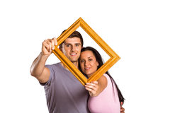 Young couple holding up frame Royalty Free Stock Photography